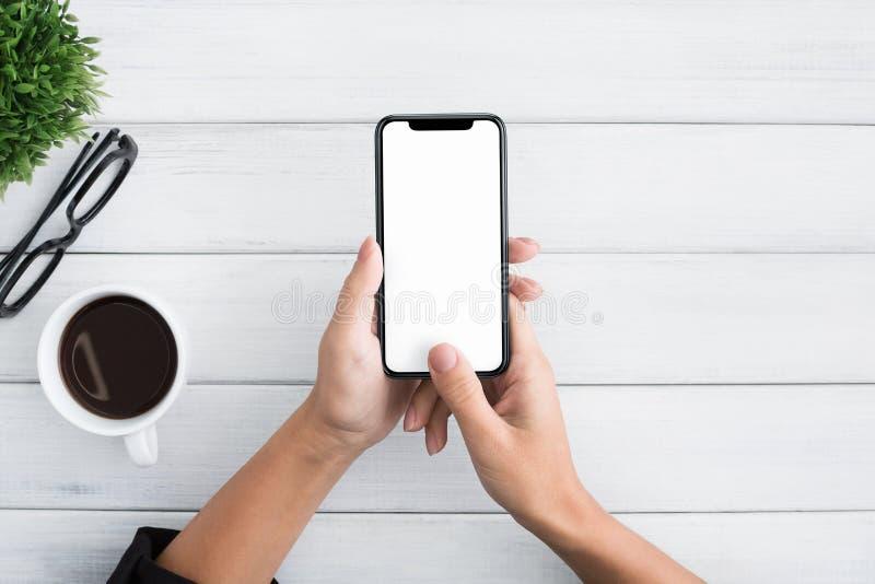 Hand die smartphone op witte houten achtergrond gebruiken stock foto's