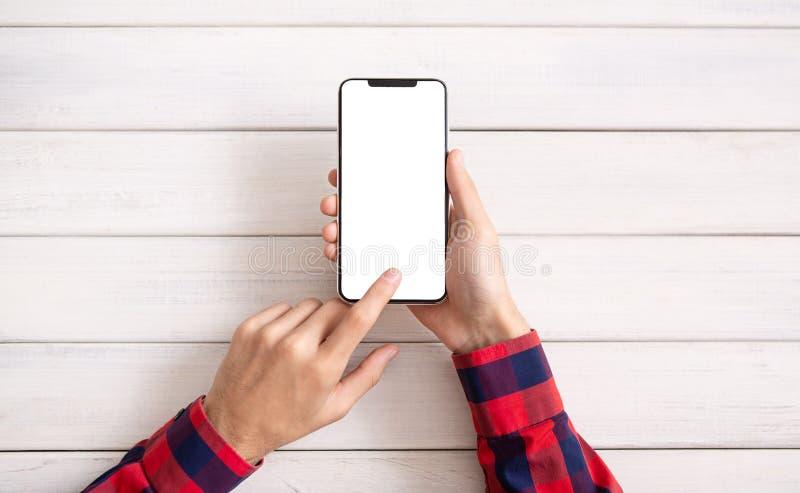 Hand die smartphone op witte houten achtergrond gebruiken royalty-vrije stock afbeeldingen
