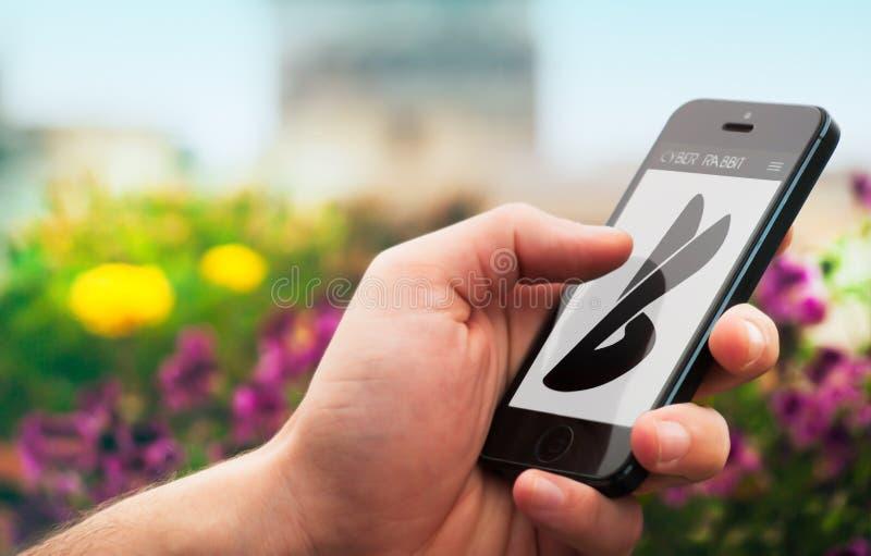 Hand, die Smartphone vom Cyber-Kaninchen hält lizenzfreies stockbild