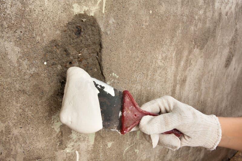 Hand, die Spachtel mit Gips hält lizenzfreie stockfotografie