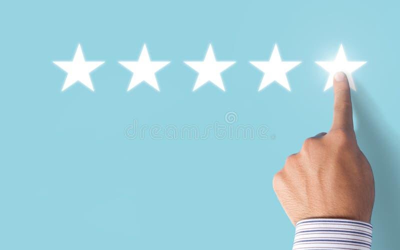 Hand, die 5 Sterne veranschlagen auf blauem Hintergrund - positives Feedback wählt stockfotografie