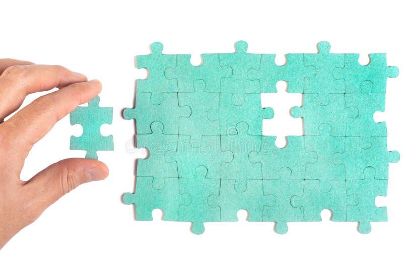 Hand die stuk van groene figuurzaag opneemt puzzlel stock afbeeldingen