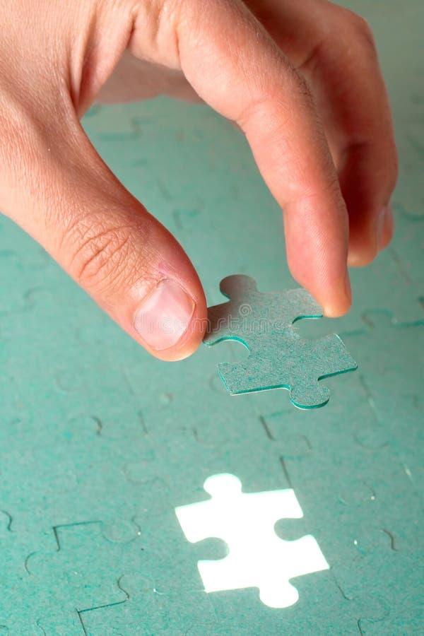 Hand die stuk van groene puzzel opneemt royalty-vrije stock fotografie