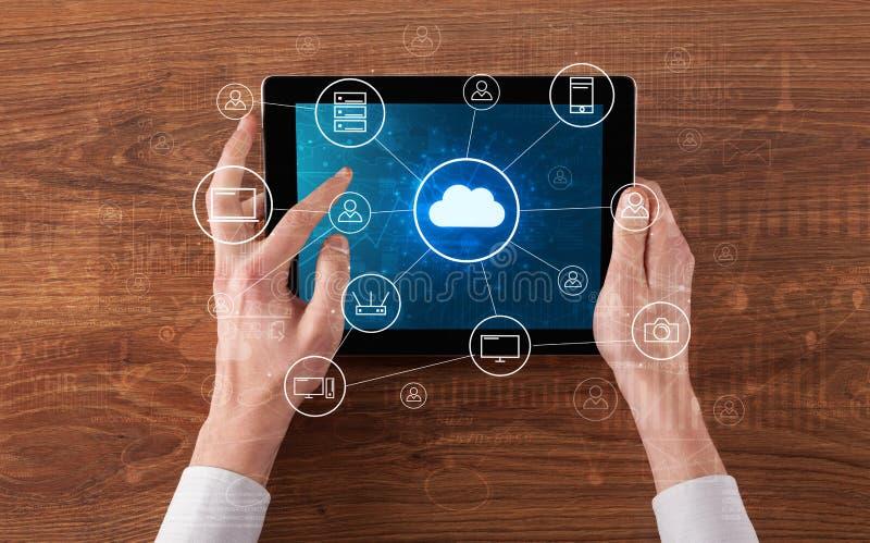 Hand die tablet met het gecentraliseerde wolk concept van het gegevensverwerkingssysteem gebruiken stock afbeeldingen