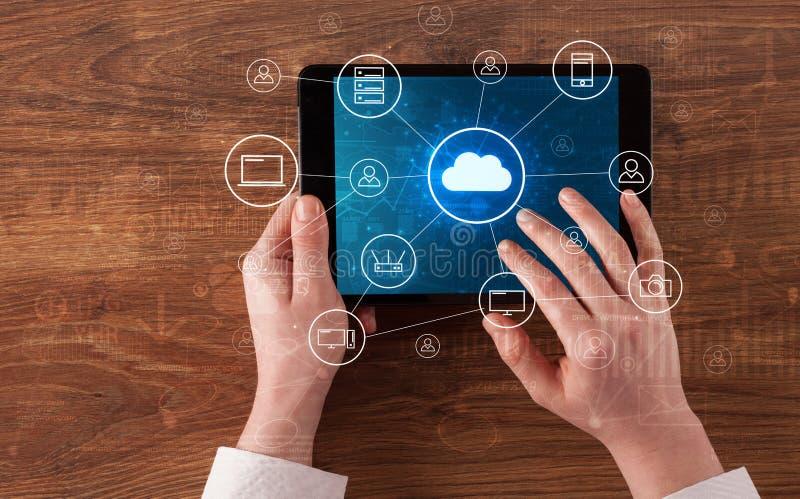 Hand die tablet met het gecentraliseerde wolk concept van het gegevensverwerkingssysteem gebruiken stock afbeelding