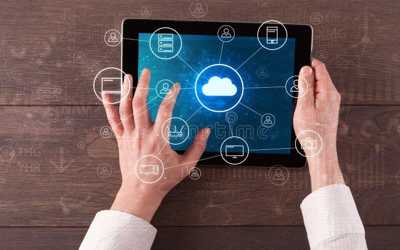 Hand die tablet met het gecentraliseerde wolk concept van het gegevensverwerkingssysteem gebruiken stock foto
