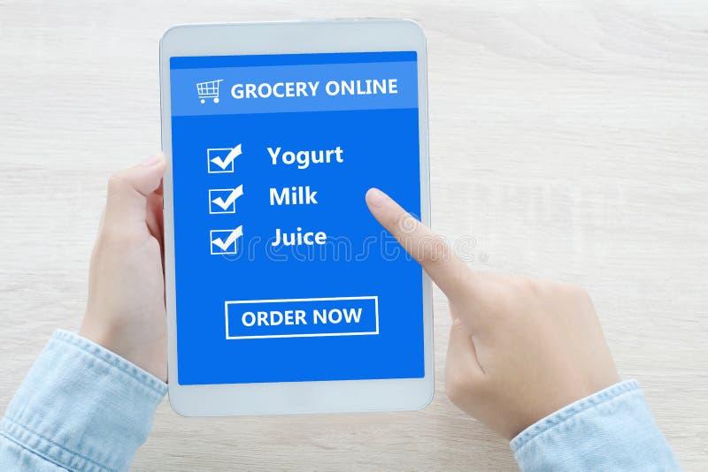 Hand die tablet met kruidenierswinkel het winkelen controlelijst online gebruiken op scr royalty-vrije stock afbeeldingen