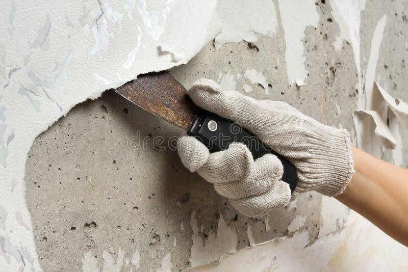 Hand, die Tapete von der Wand mit Spachtel entfernt lizenzfreies stockbild