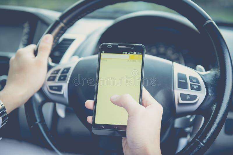 Hand die telefoon met behulp van die een tekst verzenden terwijl het drijven aan het werk stock afbeeldingen