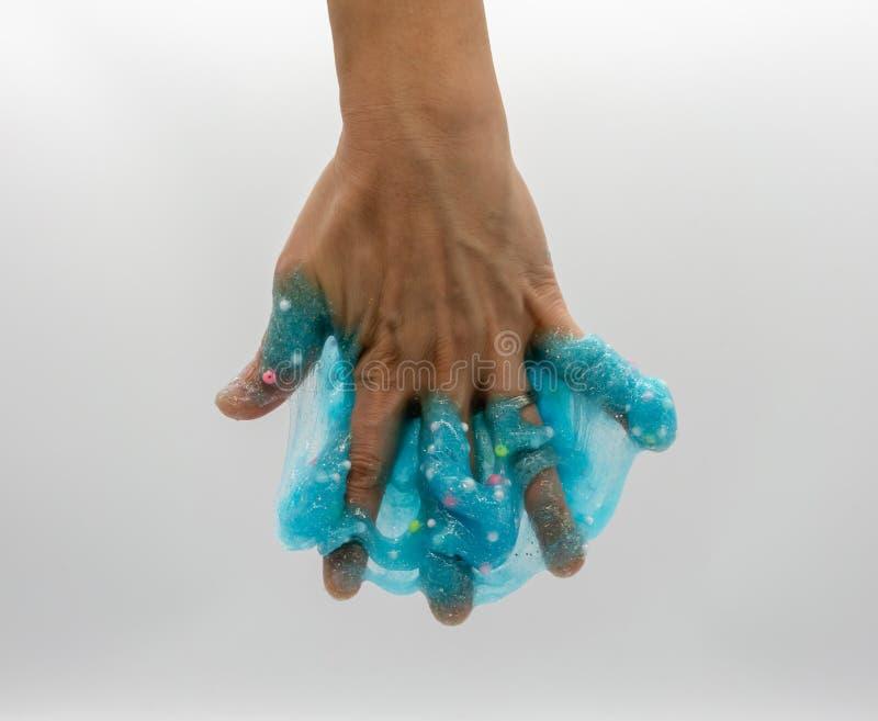 Hand die of transparant blauw spelen de doorweken schittert slijm op wit stock foto's