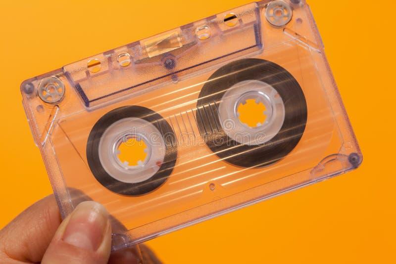 Hand, die transparente kompakte Audiokassette hält stockbild