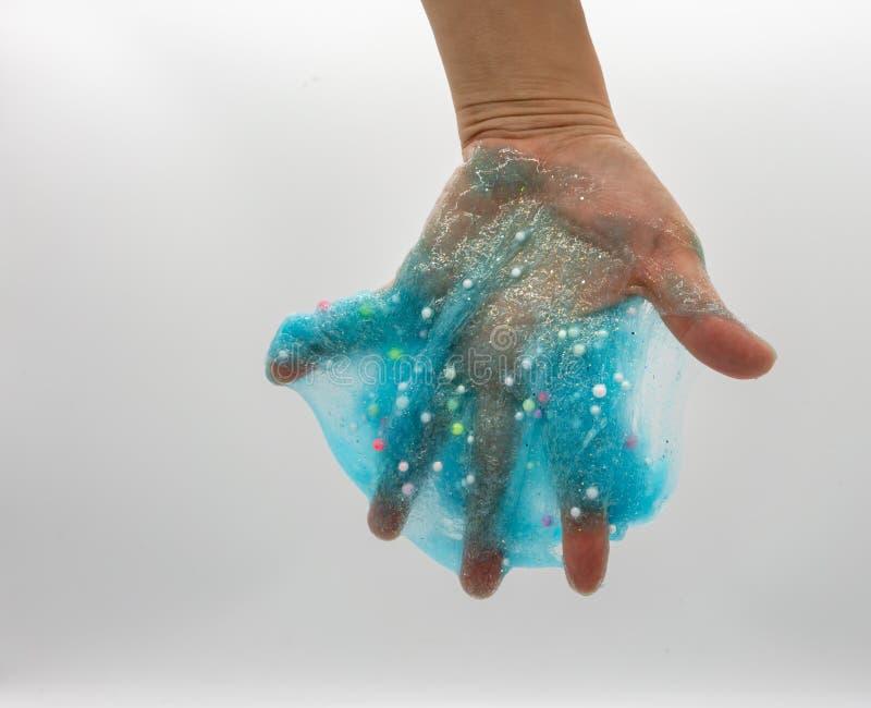 Hand, die transparenten blauen Funkelnschlamm auf Wei? spielt oder tr?nkt lizenzfreies stockbild