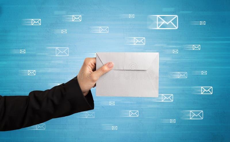 Hand, die Umschlag mit Mitteilungssymbolen herum hält stockfotografie