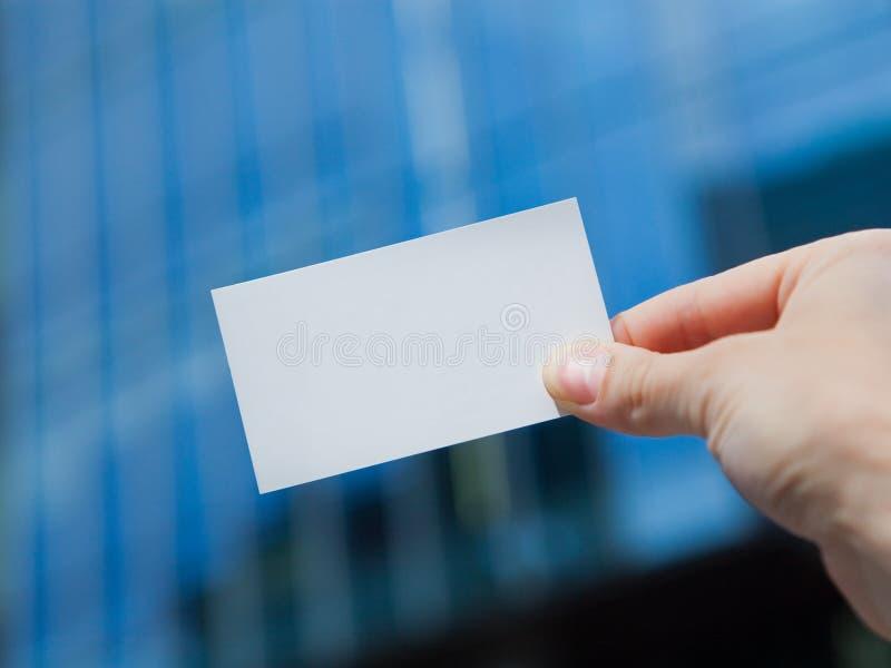 Hand, die unbelegte Besuchskarte anhält stockfotos