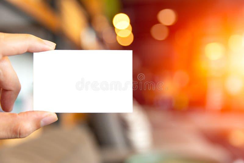 Hand, die unbelegte weiße Visitenkarte anhält stockfoto