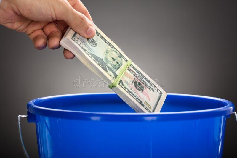 Hand, die uns Papierwährungs-Bündel im blauen Eimer wirft stockfotos