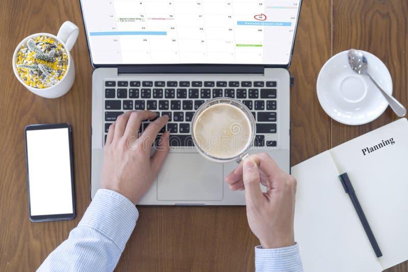 Hand die van mensenconsumptiemelk koffie en het gebruiken van computerlaptop met smartphone voor het werken aan bureau bij koffie royalty-vrije stock foto