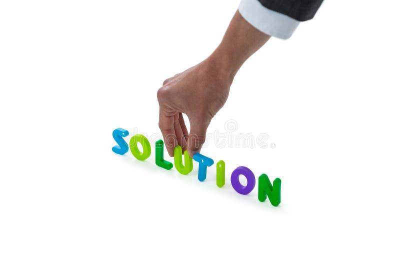 Hand die van zakenman oplossingswoord schikken royalty-vrije stock afbeelding