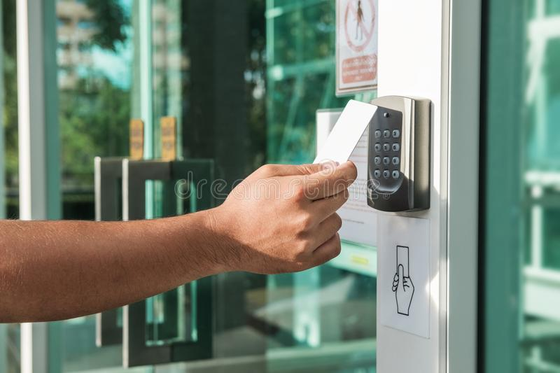 Hand die veiligheids het zeer belangrijke kaart aftasten gebruiken om de deur voor het ingaan van de privé bouw te openen Huis en stock foto
