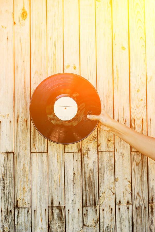 Hand, die Vinylaufzeichnung über hölzernem Hintergrund hält stockfoto