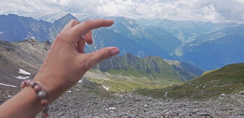 Hand die voor bergen tijdens mist en regen bereiken stock afbeeldingen