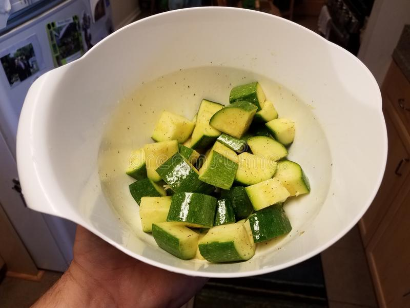 Hand, die weiße Schüssel Stücke der Zucchini hält lizenzfreie stockbilder
