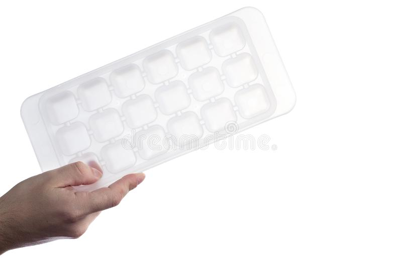 Hand, die weißen Plastikeiswürfelbehälter lokalisiert auf weißem Hintergrund hält lizenzfreie stockfotografie