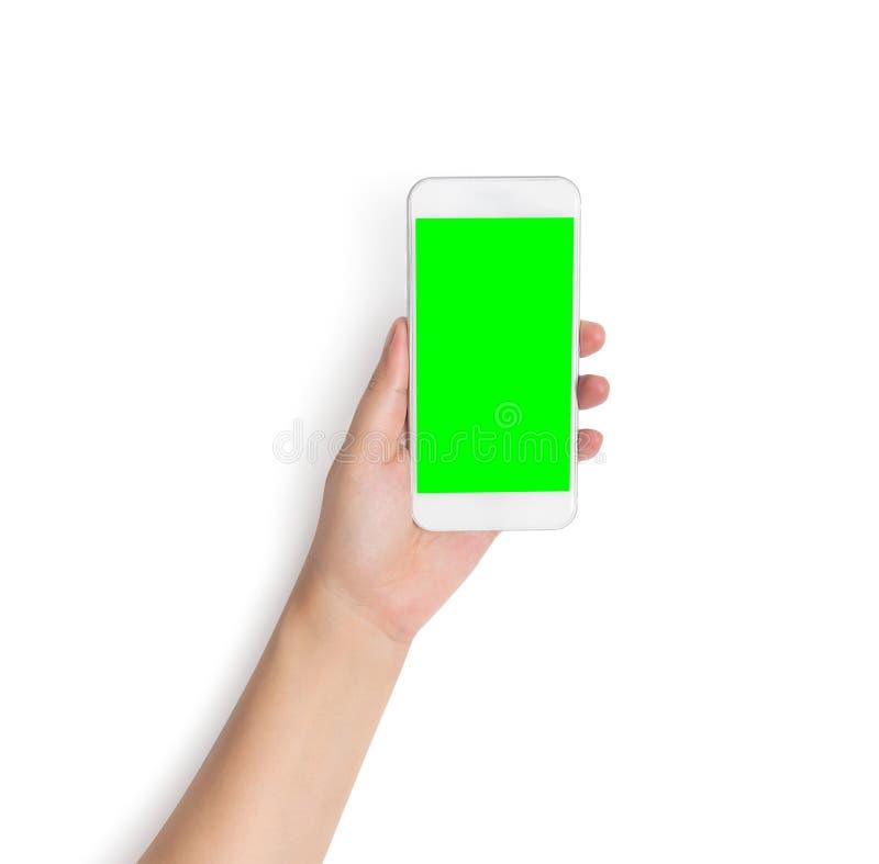 Hand, die weißes intelligentes Mobiltelefon mit dem leeren grünen Schirm lokalisiert auf weißem Hintergrund mit Beschneidungspfad lizenzfreie stockfotos