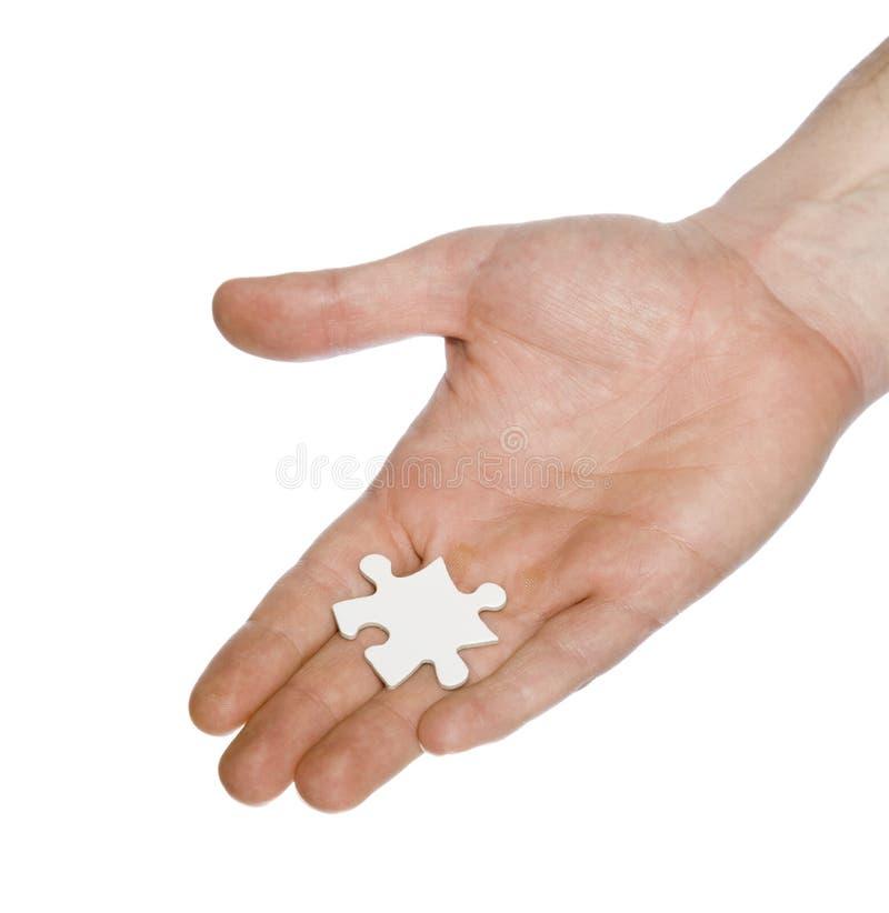 Hand, die weißes Puzzlespielstück anhält lizenzfreie stockfotografie