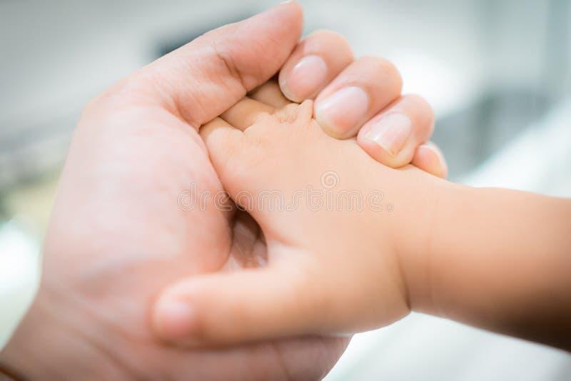 Hand die weinig babyhand met liefde houdt stock foto