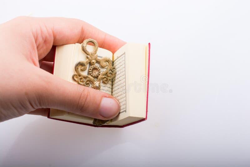 Hand die Zeer belangrijk en Islamitisch Heilig Boek Quran houden stock afbeelding