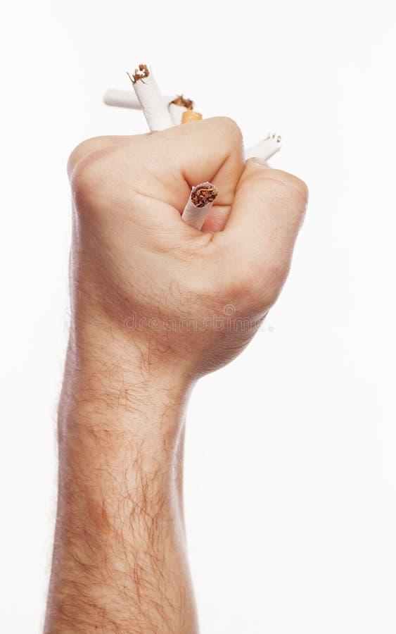 Hand, die Zigaretten zerquetscht stockfotografie