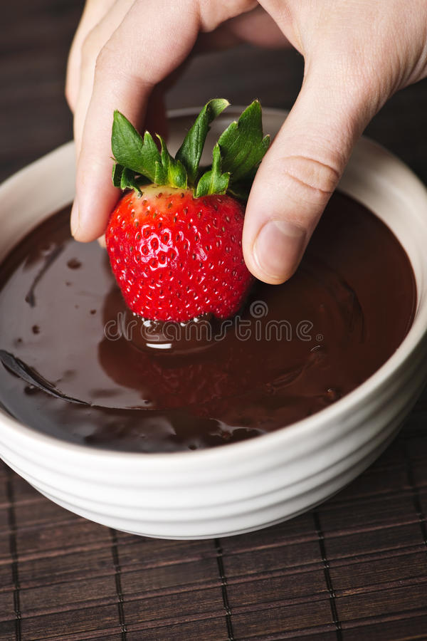 Hand dipping strawberry in chocolate royalty free stock photography