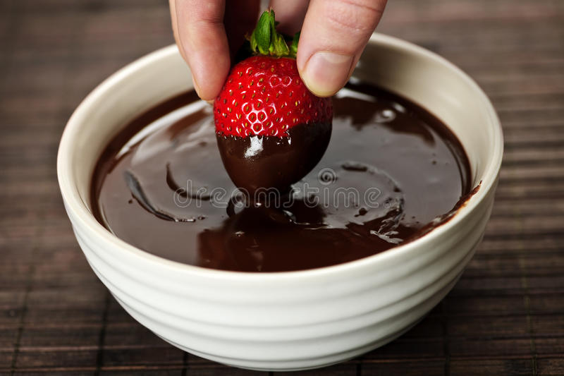 Hand dipping strawberry in chocolate royalty free stock image