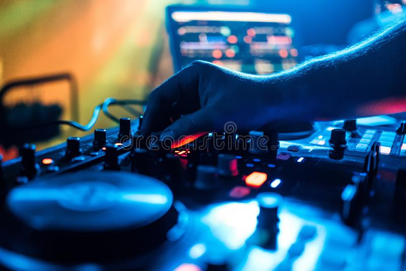 Hand of DJ moves the volume control and mixing music on a mixer. Hand of the DJ moves the volume control and mixing music on a mixer at a party in a nightclub stock images