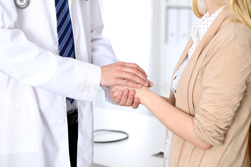 Hand of doctor reassuring her female patient. Medical ethics and trust concept.  stock image