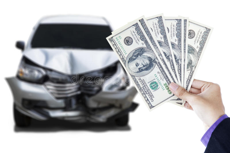 Hand with dollar currency and damaged car. Close of male hand holding dollar currency in front of a damaged car, isolated on white background royalty free stock image