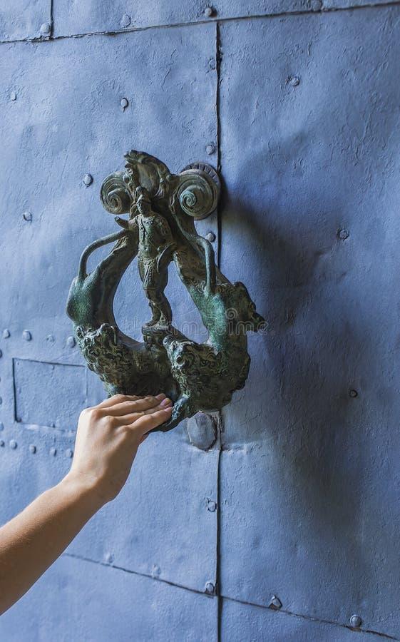 Hand on a door handle. Knocking on an old door handle stock image
