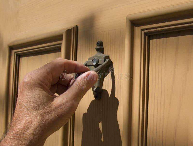 Hand on door knocker. Hand on brass door knocker stock photography