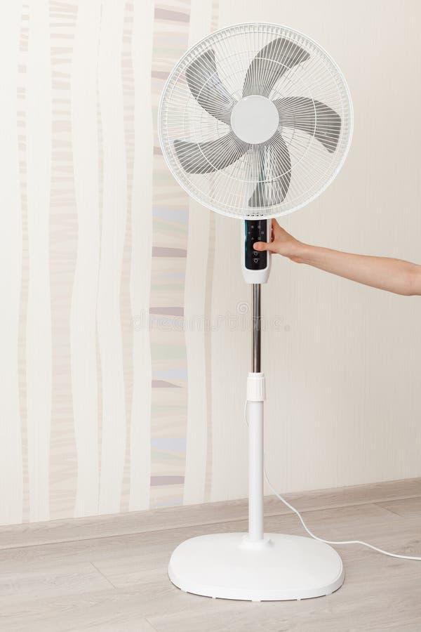 Hand drückt den Knopf auf dem Bedienfeld auf dem weißen elektrischer Ventilator Konzept: Sparen Sie Energie, retten Sie Welt, spa lizenzfreies stockfoto