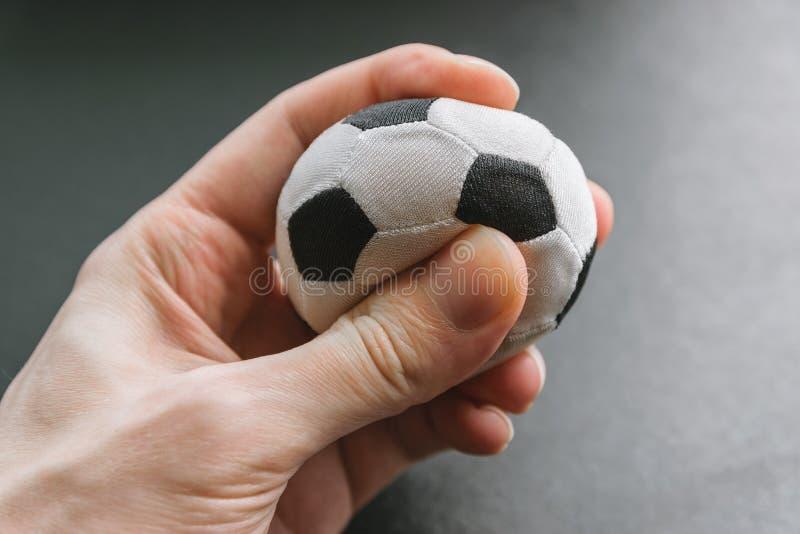 Hand drückt einen kleinen Fußball zusammen lizenzfreie stockfotografie