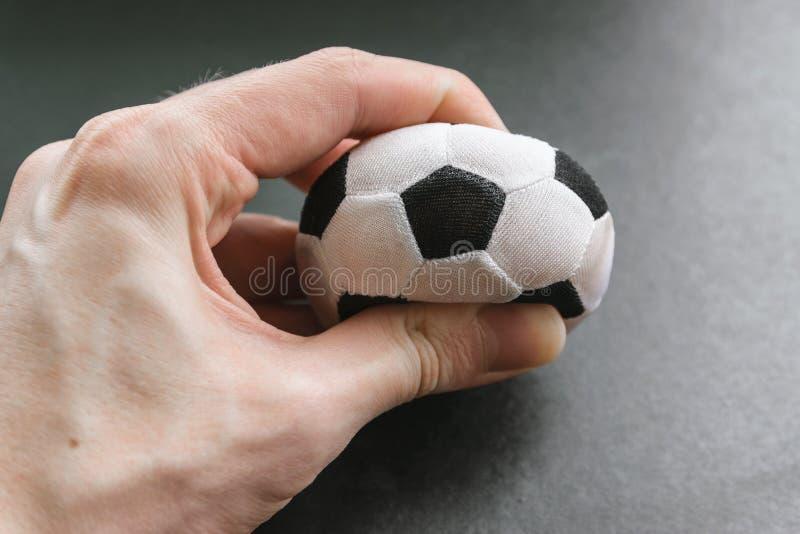 Hand drückt einen kleinen Fußball zusammen lizenzfreies stockfoto