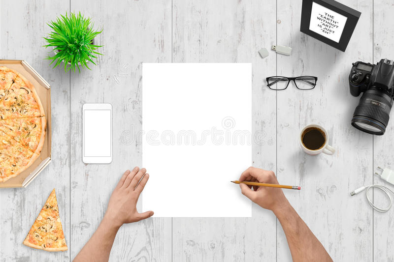 Hand drawing on empty paper. Top view of designer, author desk. White smart phone with blank screen for mockup stock photos
