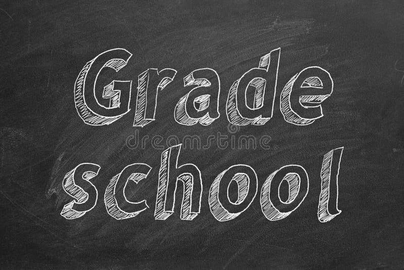 Grade school. Hand drawing `Grade school` on black chalkboard royalty free stock photography