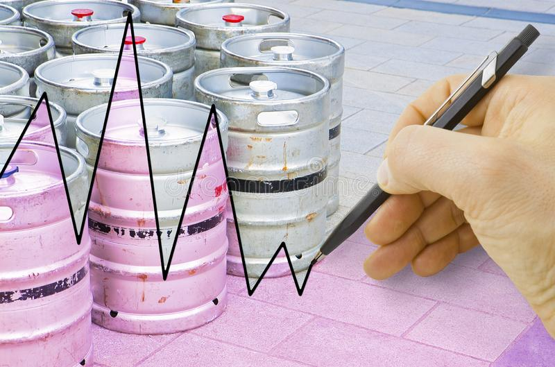 Hand drawing a graph about the trend of beer production with kegs of beer on background. Hand drawing a graph about the trend of beer .production with kegs of stock photos