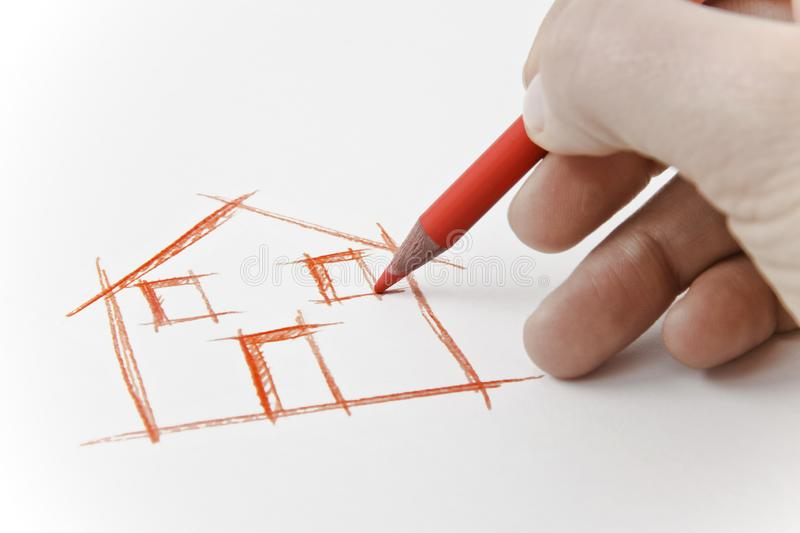 Hand drawing an house with a pencil on white sheet.  stock images