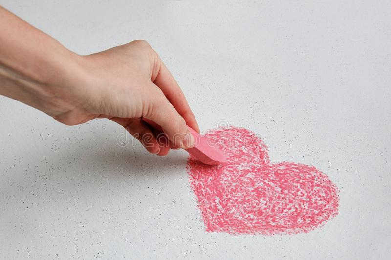 Hand drawing red heart on white wall with chalk stock photo