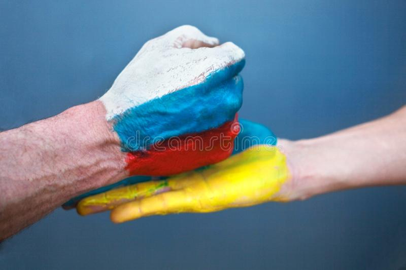 The hand with the drawing of the Russian flag hits on a hand with the drawing of the Ukrain flag royalty free stock photos