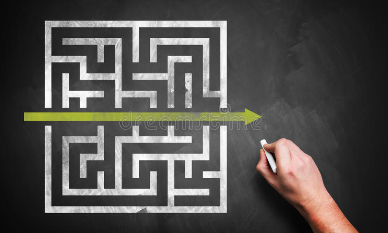 Hand drawing a shortcut to a maze. On a chalkboard stock photography