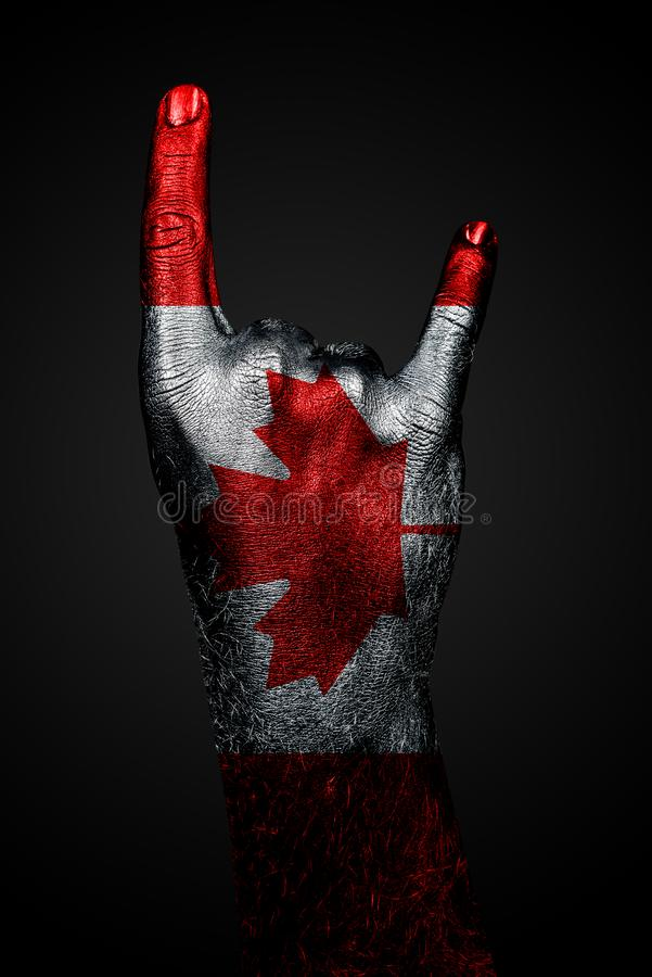 A hand with a drawn Canada flag shows a goat sign, a symbol of mainstream, metal and rock music, on a dark background stock photos